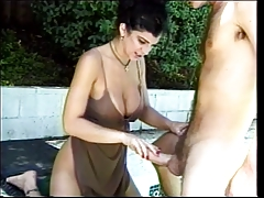 Big breasted brunette gives blowjob by the pool